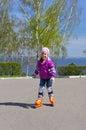 Little girl rides roller skates at park Stock Photo