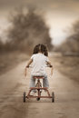 Little girl riding away on her tricycle a cute a dirt road a Stock Photo