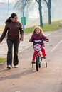 Little girl riding a bike, bycicle with mother Royalty Free Stock Images