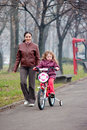 Little girl riding a bike, bycicle with mother 2 Royalty Free Stock Photo