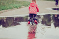 Little girl riding bike in water puddle Royalty Free Stock Photo