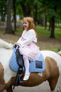 Little girl riding on a pony in a city park Royalty Free Stock Photo