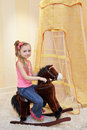 Little girl rocks on rocking horse in play room Stock Image