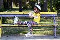 Little girl with roller skates drink water sitting on bench and Stock Photography