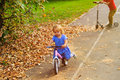 Little girl on runbike and boy at scooter in autumn, kids sport Royalty Free Stock Photo
