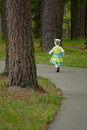 Little girl running away along a road in a park Stock Photos