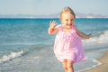 Little girl running on the beach Stock Images
