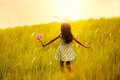 Little girl running on meadow with sunset outdoor portrait Royalty Free Stock Images