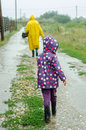 Little girl running in the rain after her granny Stock Images