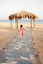 Little girl running to the sea rear view summer holidays Stock Photos