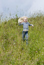 Little girl runs on meadow Stock Photos