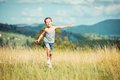 Little girl runs through a meadow happy beautiful in the mountains Royalty Free Stock Photos