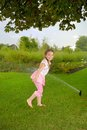Little girl runs in park under water splashes on green grass Royalty Free Stock Photography