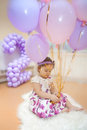 Little girl s birhtday sitting on a fur carpet with balloons Royalty Free Stock Images