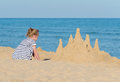 Little girl with sand castle on the beach Royalty Free Stock Images