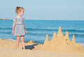 Little girl with sand castle on the beach Stock Photo
