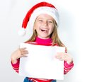 Little girl in santa claus hat cute with a white sheet of paper Royalty Free Stock Image