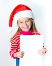 Little girl in santa claus hat with a white sheet of paper Stock Photo