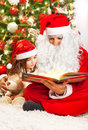 Little girl with santa claus image of reading book clause small child grandpa wearing red festive costume sitting on the floor Royalty Free Stock Photo