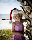 Little girl in santa hat on beach pink bathing suit and standing next to palm tree Stock Photography