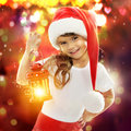 Little girl in santa hat holding red christmas happy lantern with colorful lights on background holidays new year x mas Stock Photo