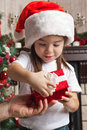 Little girl in santa hat opens red gift box for christmas in fat from father Stock Photos