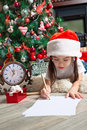 Little girl in santa hat writes letter to santa funny near christmas tree and clock Stock Photos