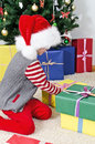 Little girl in santa s hat unpacking christmas gifts Stock Images