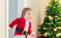 Little girl in a santa suit dashing to open her Christmas presents Royalty Free Stock Photo
