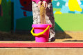 Little girl scattering sand cute in the pink bucket Stock Images