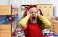 Little girl screaming at home with her ears covered by hands Royalty Free Stock Photography