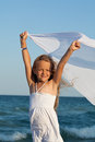 Little girl on sea shore playing with a kerchief in the wind white dress cloth Royalty Free Stock Photo