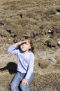Little girl shading eyes a her on a mountain track in bucegi mountains romania Royalty Free Stock Photo