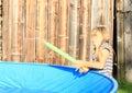 Little girl shooting with water gun barefoot hairy kid splashing by blue pool Royalty Free Stock Image