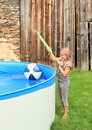 Little girl shooting with water gun barefoot hairy kid splashing by blue pool an inflating ball on surface Royalty Free Stock Photo