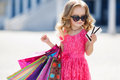 Little girl with shopping bags goes to the store Royalty Free Stock Photo
