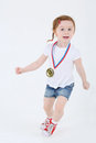 Little girl in shorts with medal on her chest runs white background motion blur Royalty Free Stock Image