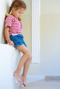 Little girl in shorts sitting Royalty Free Stock Photo