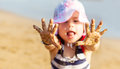 Little girl showing her hands with sand