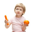 Little girl showing orange and carrot Royalty Free Stock Photo
