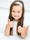 Little girl is showing thumb up gesture dressed in white using both hands Stock Images