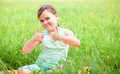 Little girl is showing thumb up gesture while sitting on green grass Royalty Free Stock Photos