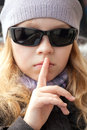 Little girl shows silence sign in sunglasses Royalty Free Stock Images