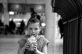 A little girl sipping milkshake in knitted dress in shopping mall Royalty Free Stock Photo