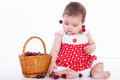 Little girl sits with  basket  cherries Royalty Free Stock Photo
