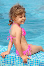 Little girl sits on border of pool Royalty Free Stock Images
