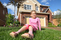 Little girl sits on grass near cottage and smiles Royalty Free Stock Photo