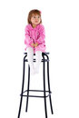 The little girl sits on a high chair Royalty Free Stock Photo