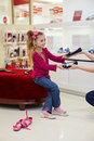 Little girl sits in new shoes and takes another one pair on ottoman from female hands Royalty Free Stock Photo