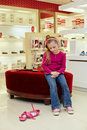 Little girl sits on ottoman in new shoes and looks at old pair Royalty Free Stock Photo